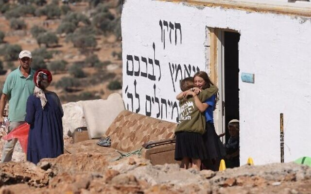 Israeli settlers bid each other farewell before evacuating the newly-established wildcat outpost of Evyatar in the West Bank, on July 2, 2021. (Photo by Emmanuel DUNAND / AFP)