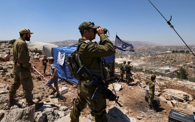 Israeli soldiers observe the Palestinian village of Beita with binoculars as settlers evacuate the newly-established wildcat outpost of Evyatar near the northern Palestinian city of Nablus in the West Bank, on July 2, 2021 (Emmanuel DUNAND / AFP)
