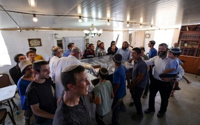 Israeli settlers dance inside a makeshift synagogue before evacuating the newly-established wildcat outpost of Evyatar in the West Bank, on July 2, 2021. (Photo by Emmanuel DUNAND / AFP)