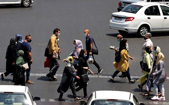Iranians, mask-clad due to the coronavirus pandemic, cross a street in the capital Tehran, on July 3, 2021. (Atta Kenare/AFP)
