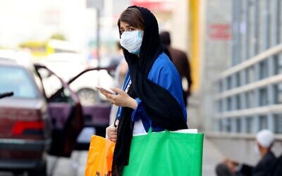 An Iranian woman, mask-clad due to the coronavirus pandemic, waits to cross a street in the capital Tehran, on July 3, 2021 (ATTA KENARE / AFP)