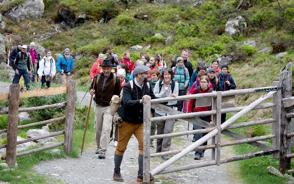Spectators are seen following the theatre group Teatro Caprile at the Windbach Alp in the Krimmler Tauern Alps on the border between Austria and Italy towards the Krimmler mountain pass, near Krimml, on June 25, 2021.(ALEX HALADA/AFP)