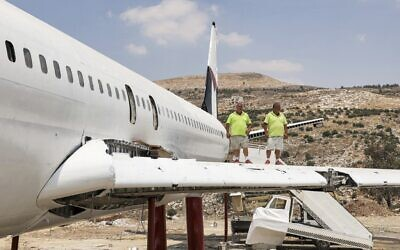 Palestinian twin brothers Atallah and Khamis al-Sairafi, 60, stand together on the wing of a Boeing 707 aircraft being converted into a restaurant near the city of Nablus in the West Bank on July 5, 2021. (Photo by JAAFAR ASHTIYEH / AFP)