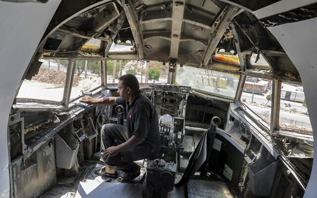 A technician drills holes in the cockpit of Boeing 707 aircraft being converted by Palestinian twin brothers Atallah and Khamis al-Sairafi into a restaurant near the city of Nablus in the West Bank on July 5, 2021. (Photo by JAAFAR ASHTIYEH / AFP)
