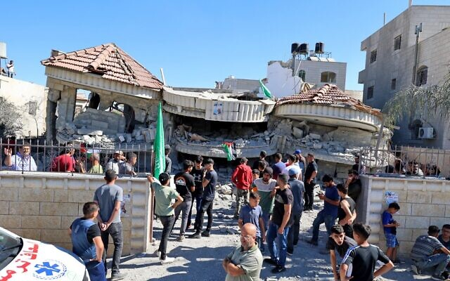 Palestinians gather outside a building that belonged to Muntasir Shalabi, accused of killing an Israeli student in a May terror attack, after it was demolished by Israeli forces in the village of Turmus Ayya near Ramallah in the West Bank on July 8, 2021 (JAAFAR ASHTIYEH / AFP)
