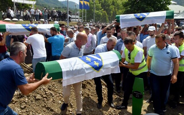 Bosnian Muslims, survivors and family members of the victims of Srebrenica 1995 massacre, carry caskets with the remains of their relatives during a burial ceremony at the memorial cemetery in village of Potocari, near the Bosnian town of Srebrenica, July 11, 2021. (Elvis Barukcic/AFP)