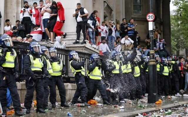 A line of police officers are the target of beer can throwers as England supporters stand around the edges of Trafalgar Square during a live screening of the UEFA EURO 2020 final soccer match between England and Italy in central London on July 11, 2021. (Photo by Tolga Akmen / AFP)