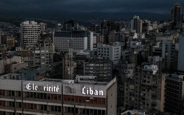 This photo taken on April 3, 2021, shows an aerial view of Lebanon's capital Beirut in darkness during power outage, with the Electricite du Liban (Electricity Of Lebanon) national company headquarters in the foreground. (Dylan COLLINS / AFP)