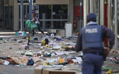 A looter smiles as she runs away from a member of the South African Police Services (SAPS) inside the Lotsoho Mall in Katlehong  township, East of Johannesburg, on July 12, 2021. (Phill Magakoe / AFP)