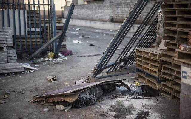 The body of a man believed to have been killed overnight lies at the scene of a looted mall in Vosloorus, on the outskirts of Johannesburg on July 14, 2021. (MARCO LONGARI / AFP)