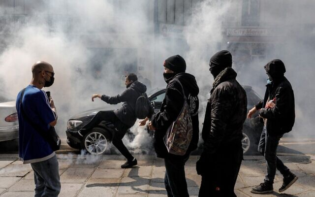 A demonstrator kicks back a gas canister to Police on the sidelines of a protest in central Paris on July 14, 2021 against a governmental decision to impose Covid-19 tests for unvaccinated people who want to eat in restaurants or take long-distance trips, as the country looks to avoid a surge in more contagious Delta cases. (GEOFFROY VAN DER HASSELT / AFP)
