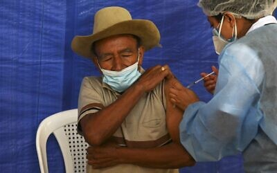 A man receives a dose of the AstraZeneca coronavirus vaccine donated by the US, at a vaccination center in San Juan Sacatepequez, Guatemala, on July 15, 2021. (Johan Ordonez/AFP)