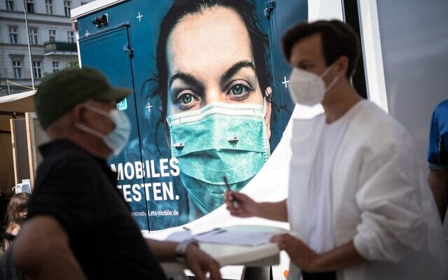 People register to get vaccinated at a mobile pop-up vaccination station at Hermannplatz square in Berlin's Neukoelln district on July 16, 2021, amid the coronavirus pandemic. (STEFANIE LOOS / AFP)