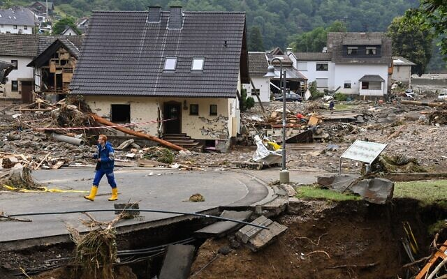 A man walk on a road amid destroyed houses after the floods caused major damage in Schuld near Bad Neuenahr-Ahrweiler, western Germany, on July 16, 2021 (CHRISTOF STACHE / AFP)