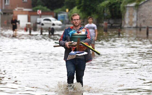 A local resident walks in a flooded street in Angleur, near Liege, on July 16, 2021. The situation remains critical as the water keep rising after the heavy rainfall of the previous days (JOHN THYS / AFP)
