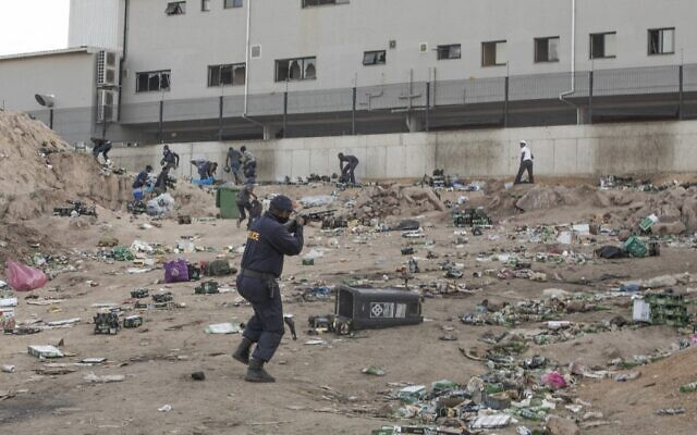 A member of the South African Police Service shoots rubber bullets to disperse looters outside a a warehouse storing alcohol in Durban on July 16, 2021, in the midst of an ongoing alcohol ban after protestors have clashed with police following a week of unrest in South Africa. (Guillem Sartorio/AFP)