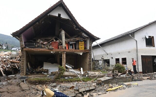 A man stands in front of a destroyed house after floods caused major damage in Schuld near Bad Neuenahr-Ahrweiler, western Germany, on July 17, 2021. (CHRISTOF STACHE / AFP)