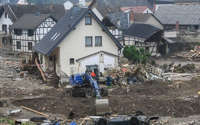 An excavator digs a hole next to a car that lies upside down after the floods caused major damage in Schuld near Bad Neuenahr-Ahrweiler, western Germany, on July 17, 2021. (Christof Stache/AFP)