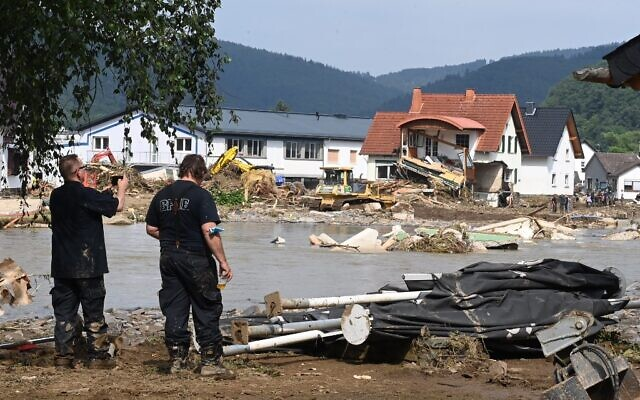 A worker (L) takes a picture of a destroyed area in Insul near Bad Neuenahr-Ahrweiler, western Germany, on July 17, 2021. (Photo by CHRISTOF STACHE / AFP)