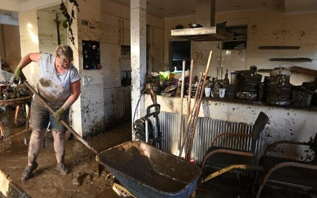 A local resident shovels mud to clear a house in Bad Neuenahr-Ahrweiler, western Germany, on July 17, 2021. (Photo by CHRISTOF STACHE / AFP)
