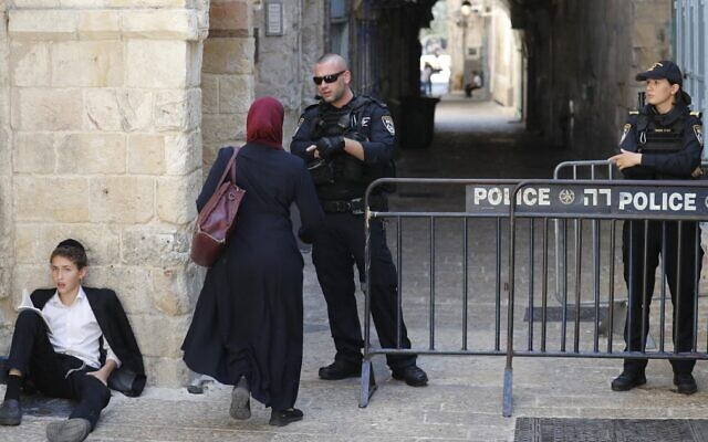 A Palestinian woman approaches a checkpoint as an ultra-Orthodox Jewish teen prays outside the al-Aqsa mosque compound in Jerusalem, during the annual Tisha B'Av fast day on July 18, 2021. (AHMAD GHARABLI / AFP)