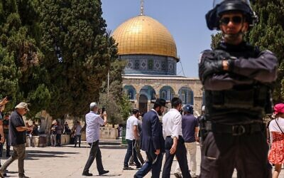 A member of the Israeli security forces stands guard as a group of Jews enters the Temple Mount in Jerusalem, during the annual Tisha B'Av fast day, on July 18, 2021. (Ahmad Gharabli/AFP)