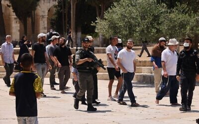 Israeli security forces stand guard as a group of Jews enter the Temple Mount in Jerusalem's Old City, during the Tisha B'Av fast mourning the destruction of the temples, on July 18, 2021. (Ahmad Gharabli/AFP)