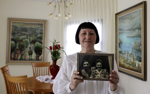 Shoshana Greenberg, 74, the daughter of a Holocaust survivor, poses for a picture holding a portrait of her parents Regina and Israel, at her home in Israeli city of Tel Aviv on July 18, 2021. (MENAHEM KAHANA / AFP)