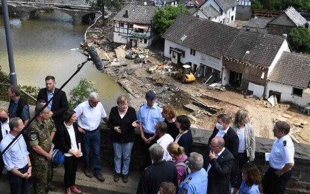 German Chancellor Angela Merkel (center left) and Rhineland-Palatinate State Premier Malu Dreyer (center right) speak to people as they stand on a bridge during their visit in the flood-ravaged areas, in Schuld near Bad Neuenahr-Ahrweiler, Rhineland-Palatinate state, western Germany, on July 18, 2021. (Christof Stache/AFP)