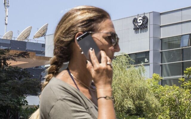Illustrative. An Israeli woman uses her phone in front of a building in Herzliya that housed the NSO Group intelligence firm, on August 28, 2016. (Jack Guez/AFP/File)