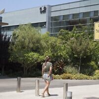 In this file photo taken on August 28, 2016, a woman walks outside the building housing the Israeli NSO group, in Herzliya. (Jack Guez/AFP)