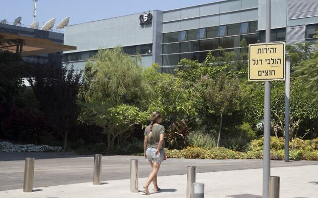 In this file photo taken on August 28, 2016, a woman walks outside the building housing the Israeli NSO group, in Herzliya. (JACK GUEZ / AFP)