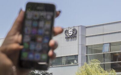 In this file photo taken on August 28, 2016, a woman uses her iPhone in front of the building housing the Israeli NSO group, in Herzliya, near Tel Aviv. (JACK GUEZ / AFP)