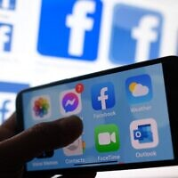 This file photo shows a Facebook App logo displayed on a smartphone in Los Angeles, March 1, 2021. (Chris Delmas/AFP)