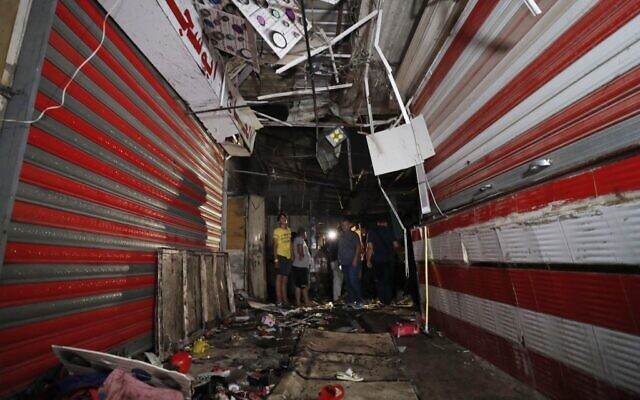 Iraqis inspect the site of the explosion in a popular market in the mostly Shiite neighbourhood of Sadr City, east of Baghdad, on July 19, 2021. (Ahmad Al-Rubaye/AFP)