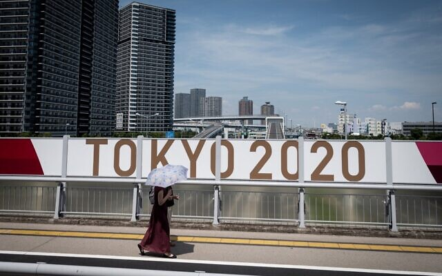 A woman walks along a street in downtown Tokyo on July 20, 2021, ahead of the Tokyo 2020 Olympic Games. (Loic VENANCE / AFP)