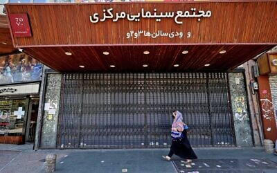 Iranians walk past a shuttered cinema hall in downtown Tehran on July 20, 2021. (ATTA KENARE / AFP)