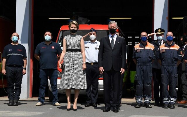 King Philippe of Belgium (C right) and Queen Mathilde of Belgium (C left) respect a minute of silence during a tribute ceremony, part of the national mourning day for victims of the severe floods, in Verviers, on July 20, 2021. (JOHN THYS / AFP)
