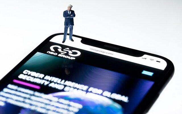 This studio photographic illustration shows a smartphone with the website of Israel's NSO Group which features 'Pegasus' spyware, on display in Paris on July 21, 2021. (Joel Saget/AFP)