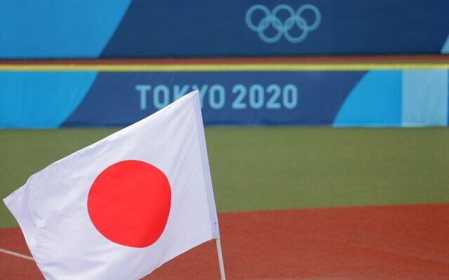 Japan's national flag is hoisted on the field prior to the Tokyo 2020 Olympic Games softball opening round game between Mexico and Japan at Fukushima Azuma Baseball Stadium in Fukushima, Japan, on July 22, 2021. (KAZUHIRO FUJIHARA / AFP)