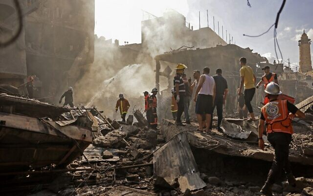 Palestinian rescuers and onlookers gather at the scene of a blast in Gaza City, the cause of which has not yet been determined, on July 22, 2021. (MOHAMMED ABED / AFP)