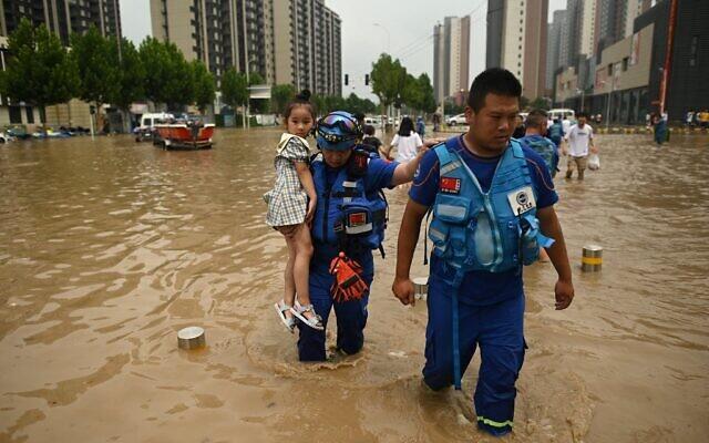 Members of rescue organization Bluesky rescue team carry a girl across a flooded street following a heavy rain in Zhengzhou, in China's Henan province, on July 22, 2021. (Noel Celis/AFP)
