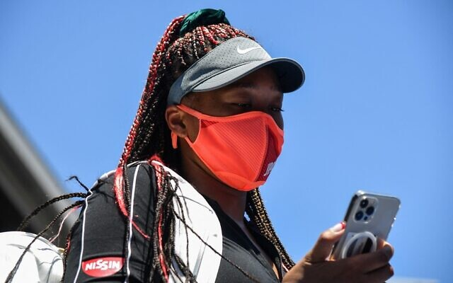 Japan's Naomi Osaka looks at her phone at Ariake Tennis Park ahead of the Tokyo 2020 Olympic Games in Tokyo on July 23, 2021. (Tiziana FABI / AFP)