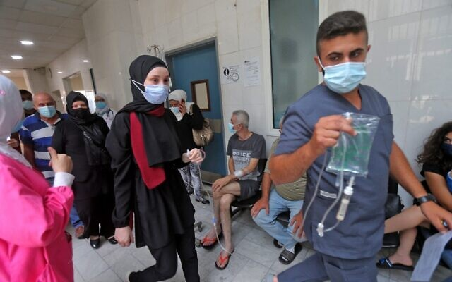 A medic assists a patient as others wait in a hallway at the Rafic Hariri University Hospital (RHUH) in Lebanon's capital Beirut on July 23, 2021. (STR / AFP)
