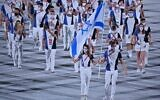 Israel's flag bearers Hanna Minenko (L) and Yakov Toumarkin lead the delegation during the opening ceremony of the Tokyo 2020 Olympic Games, at the Olympic Stadium, in Tokyo, on July 23, 2021. (Ben STANSALL / AFP)