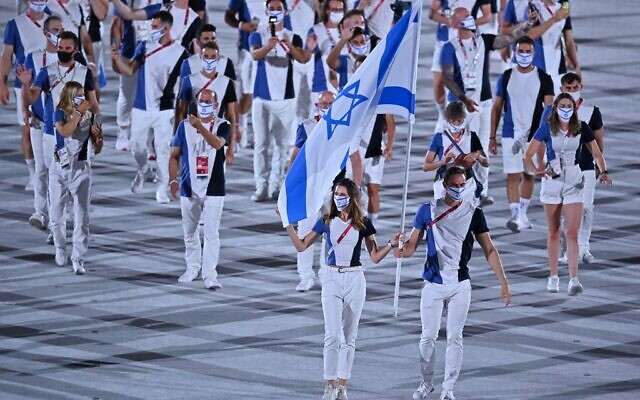 Israel's flag bearers Hanna Minenko (L) and Yakov Toumarkin lead the delegation during the opening ceremony of the Tokyo 2020 Olympic Games, at the Olympic Stadium, in Tokyo, on July 23, 2021. (Ben STANSALL/AFP)