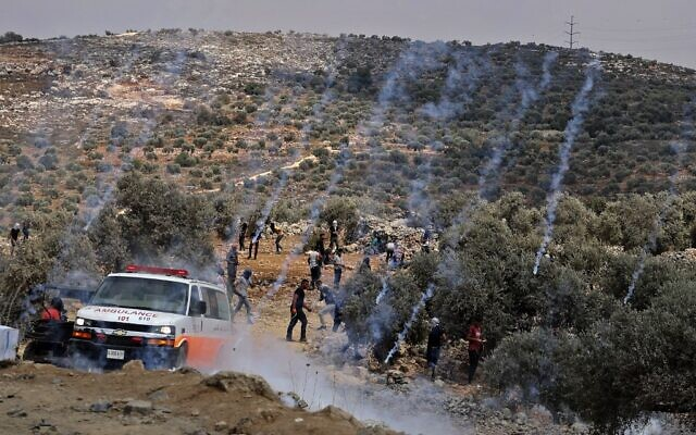 Tear gas canisters fired by Israeli forces land amidst Palestinian protesters during confrontations in the town of Beita, near the West Bank city of Nablus, on July 23, 2021, after a protest against the Israeli outpost of Eviatar. (Photo by JAAFAR ASHTIYEH/AFP)
