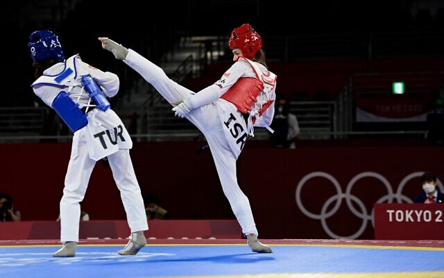 Turkey's Rukiye Yildirim (Blue) and Israel's Abishag Semberg (Red) compete in the taekwondo women's -49kg bronze medal A bout during the Tokyo 2020 Olympic Games at the Makuhari Messe Hall in Tokyo, on July 24, 2021. (Javier Soriano/AFP)
