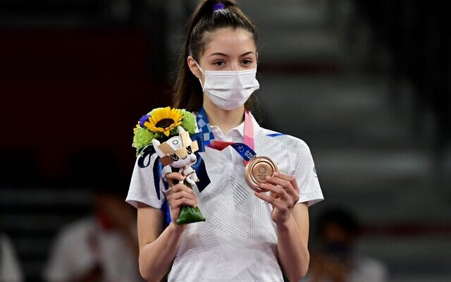 Israel's Avishag Semberg celebrates with her bronze medal on the podium after winning the taekwondo women's -49kg bronze medal A bout during the Tokyo 2020 Olympic Games at the Makuhari Messe Hall in Tokyo, on July 24, 2021. (Javier Soriano/AFP)