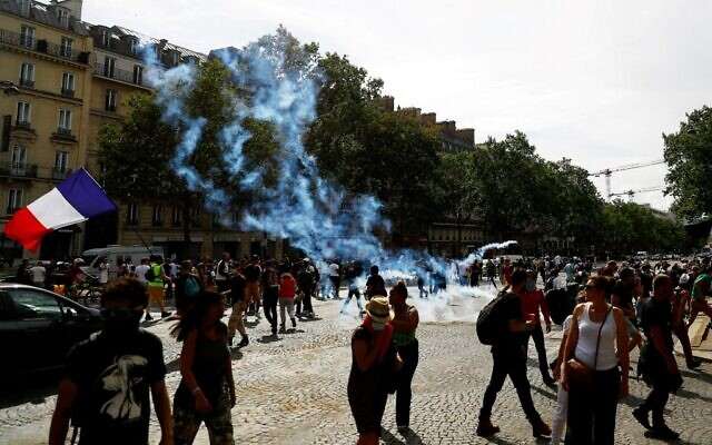 Prosters stand amidst tear gas smoke on the Champs Elysees avenue during clashes on the sidelines of a demonstration against the compulsory vaccination for certain workers and the mandatory use of the health pass called by the French government in Paris, on July 24, 2021. (Sameer Al-Doumy/AFP)